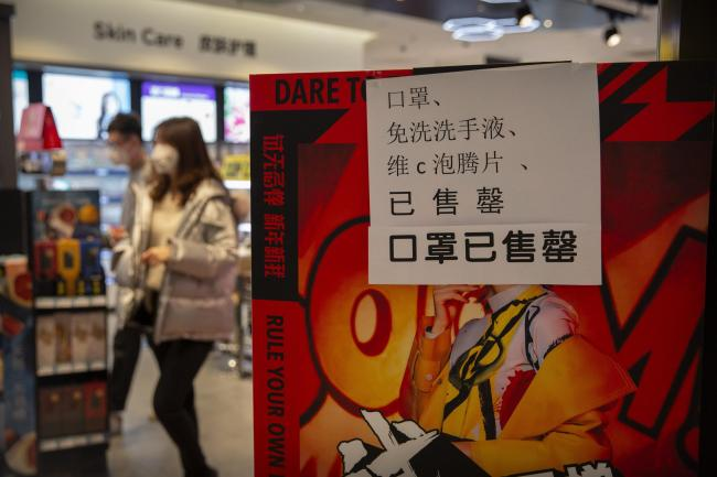 People walk past a sign at a drug store saying that it is sold out of face masks in Beijing