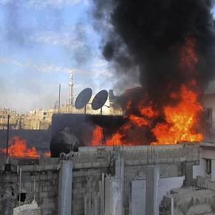 Flames rise from a house in Homs after shelling from the Syrian government (AP)