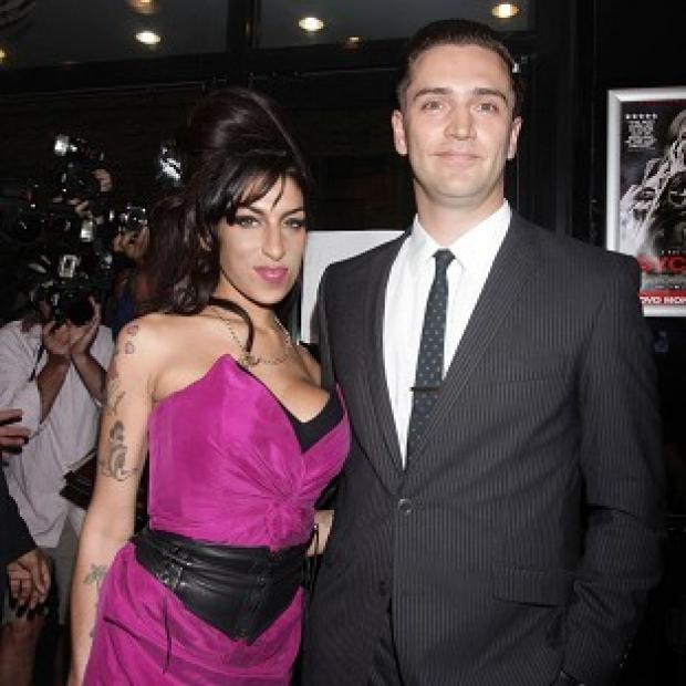Reg Traviss, pictured with his late girlfriend Amy Winehouse, will appear before magistrates next month