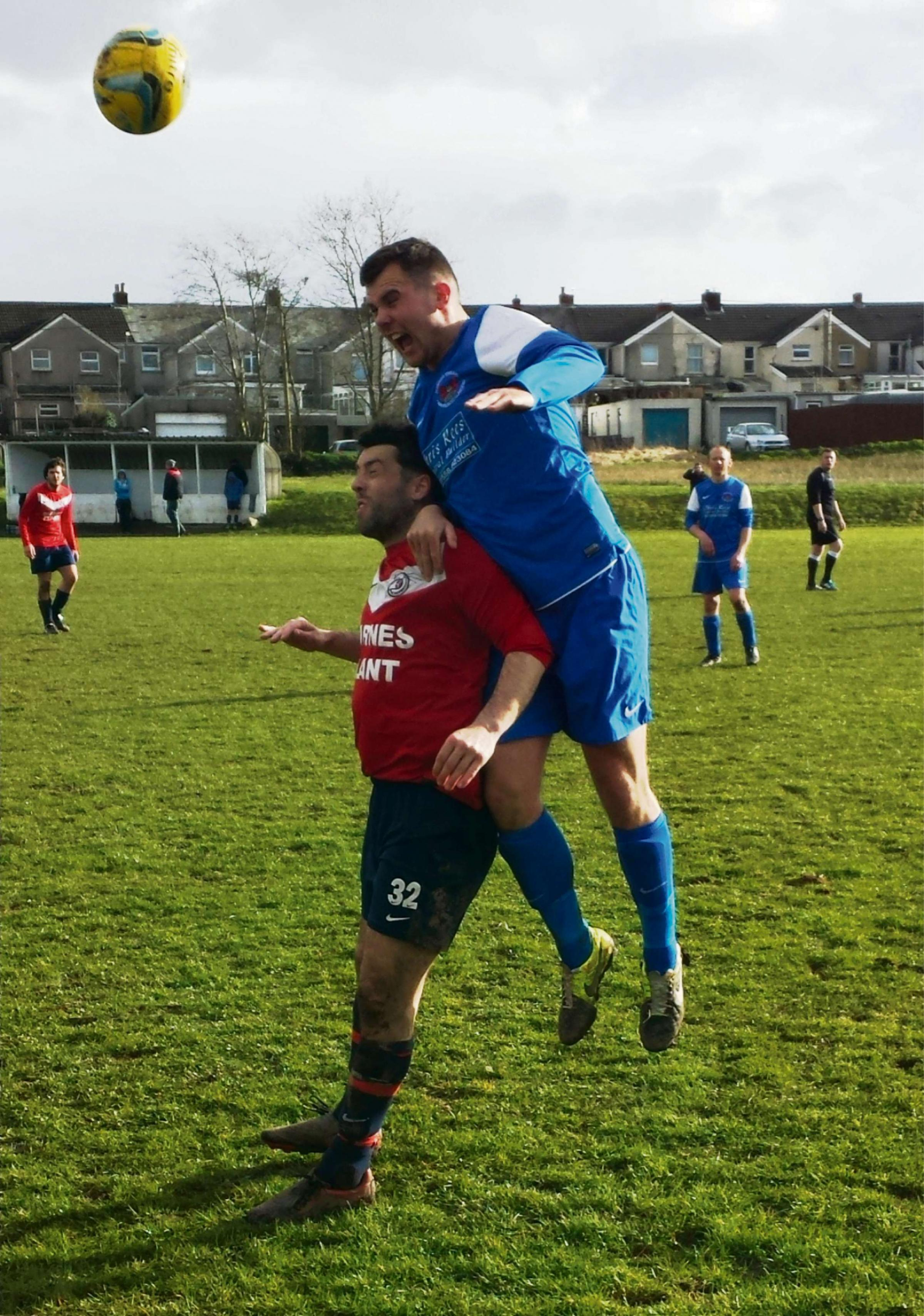 CLIMBING HIGH: Llandeilo goal-scorer Jamie Woodall towers above the Caerbryn defender in the 4-0 win.