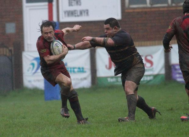 MUDDY HELL: Betws scrum half Dylan Rees is challenged by Cefn Cribbwr. Betws narrowly lost 13-10.Pic: SDD