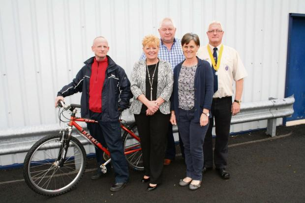 SADDLING UP: Myrddyn Griffiths is pictured with his new bike.  He is joined by (from left) Cllr Susan McNicholas, Tom Addey, Powys County Council's Area Regeneration Manager (South); Helen Davies, Sustrans; and Howard Williams, 1st Swansea Valley Sc