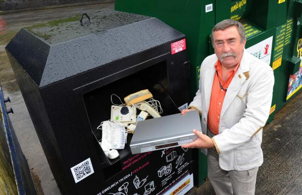 GOING FOR A WEEE: Carmarthenshire county councillor Colin Evans gets rid of an old DVD player at one of the new recycling banks for small electrical goods.