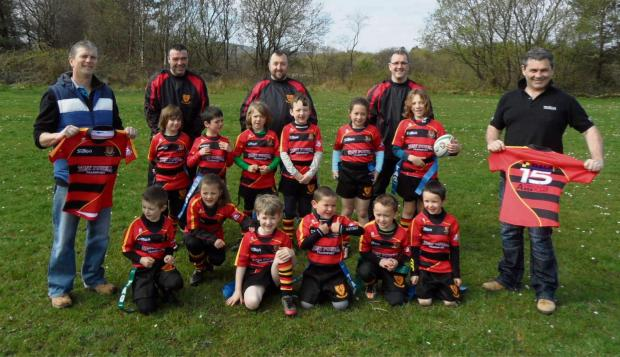 NEW SHIRTS: Mark Powell, executive director of Tony Powell Transport, and Richard Sutton, of Sutton Brothers, joined coaches Andrew Thomas, Middle Robert Evans and Richard Jones to hand over new kits to Penygroes RFC Under-7s and Under-8s. Other sponsors