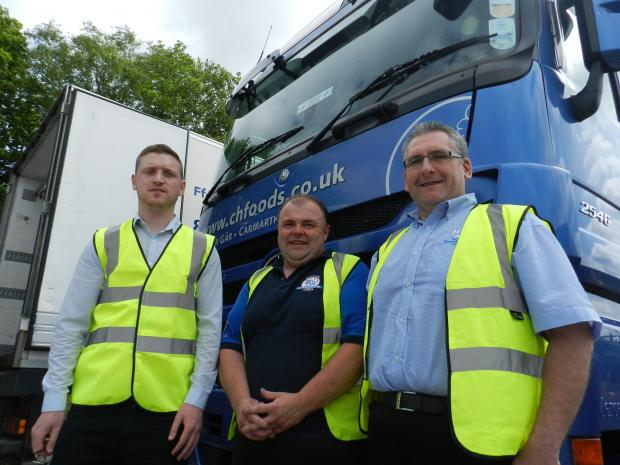 WORKING HARD: Carmarthenshire People First Job Club's Tom Clarke, driver's mate Simon Batten and Johnny Harries, Transport Manager at Castell Howell Foods of Cross Hands, get down to business.