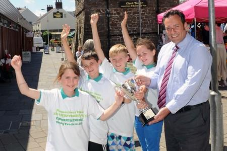 TOP TRADERS: Ysgol Llangadog, the winning team of Carmarthenshire Young traders 2014 competition, being presented with their trophy by Carmarthenshire County Council's head of co-operate property Jonathan Fearn.
