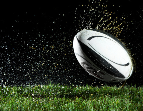 Rugby ball in motion over grass.