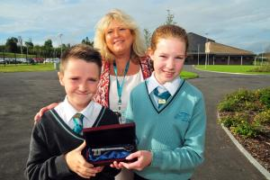 South Wales Guardian: Key to the Future - Year 7 School Council representatives Lois Davies and Rhys Atkins receive the Commemorative School Key at the official opening of Ysgol Bro Dinefwr from Headteacher Julie Griffiths.  Picture by Mark Davies