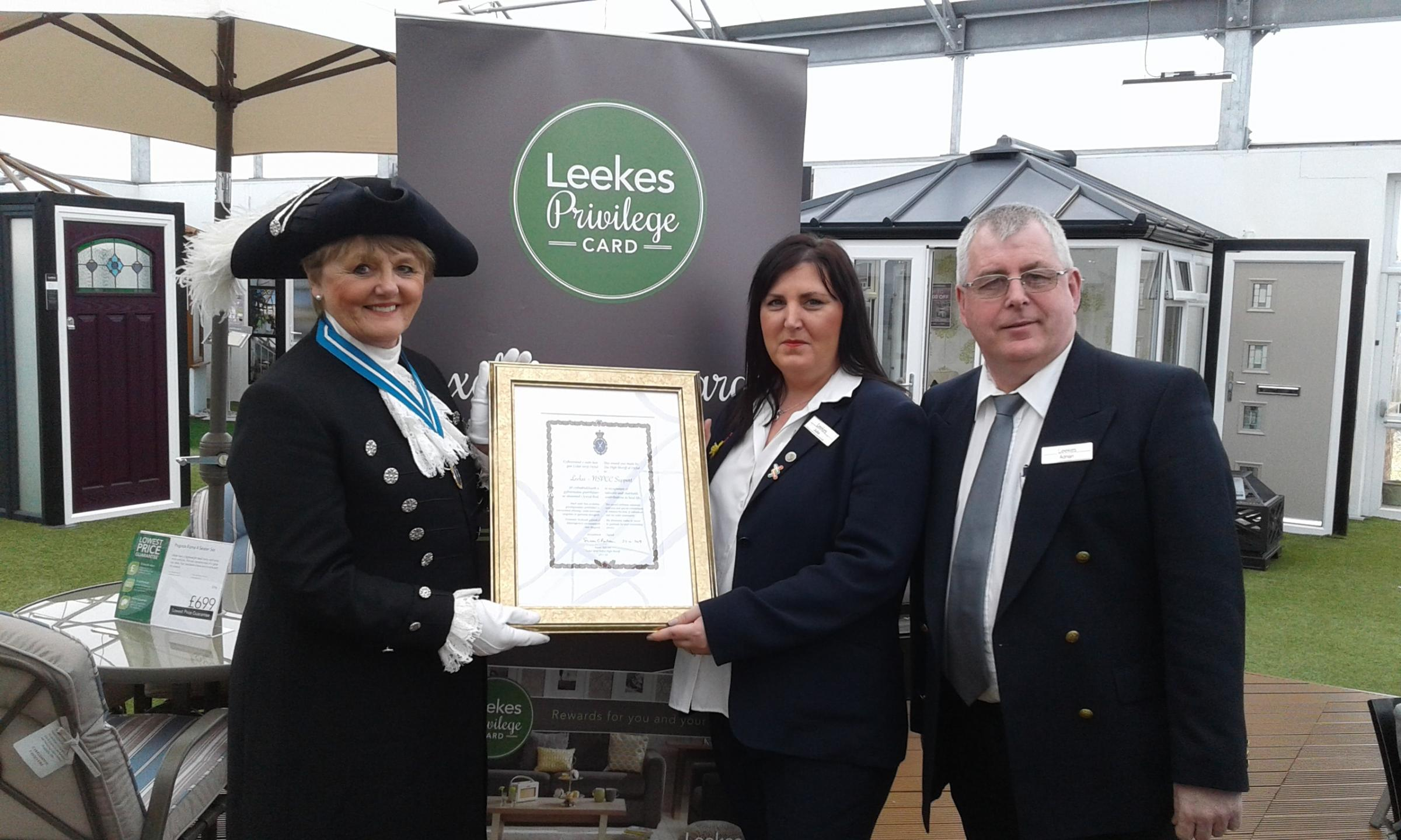 High Sheriff of Dyfed, Mrs Susan Balsom presents the award to Julie Roberts and Adrian Evans of Leekes
