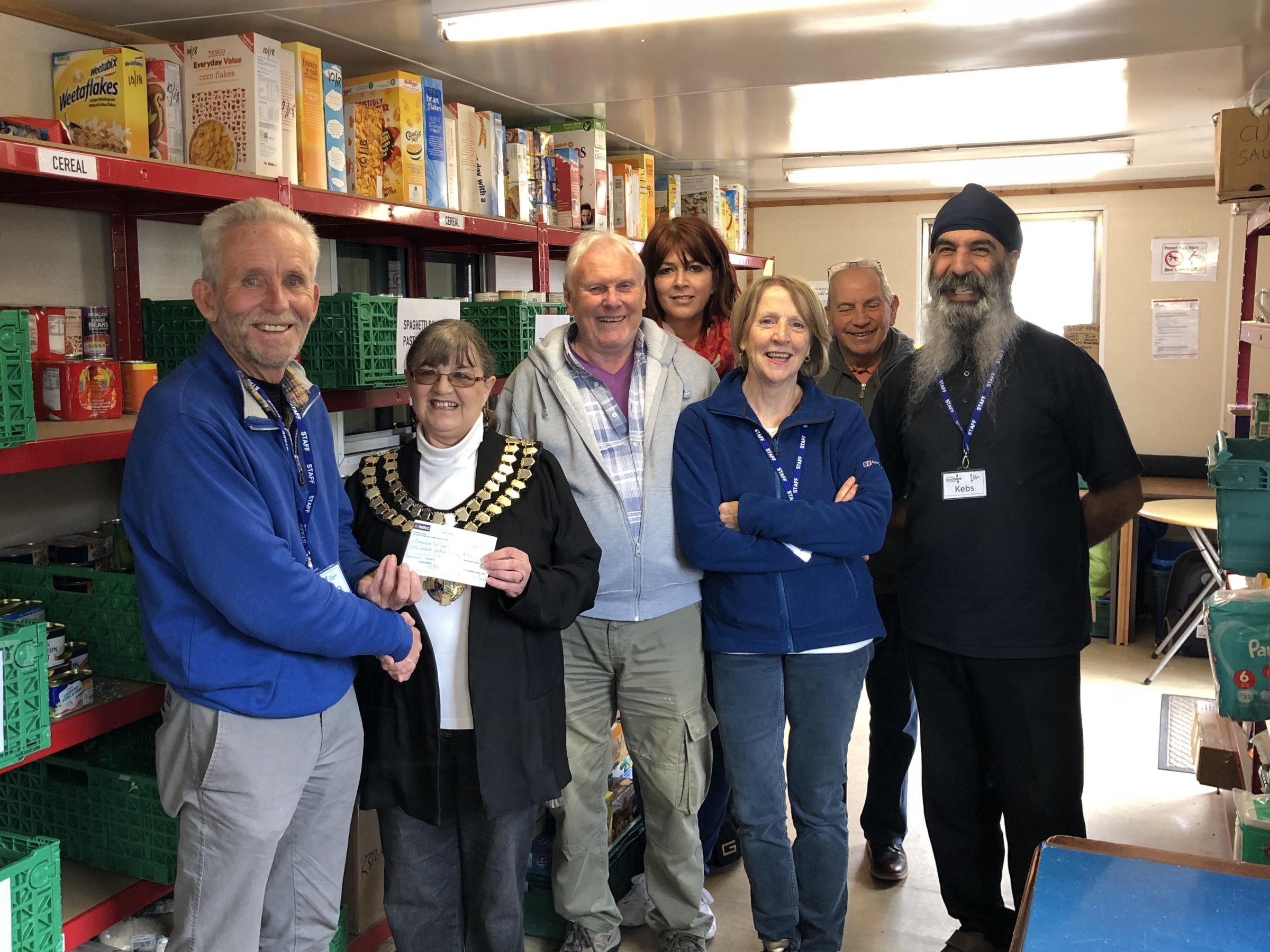Cwmaman Mayor Pauline Barker presents Ammanford Foodbank a cheque of £100.