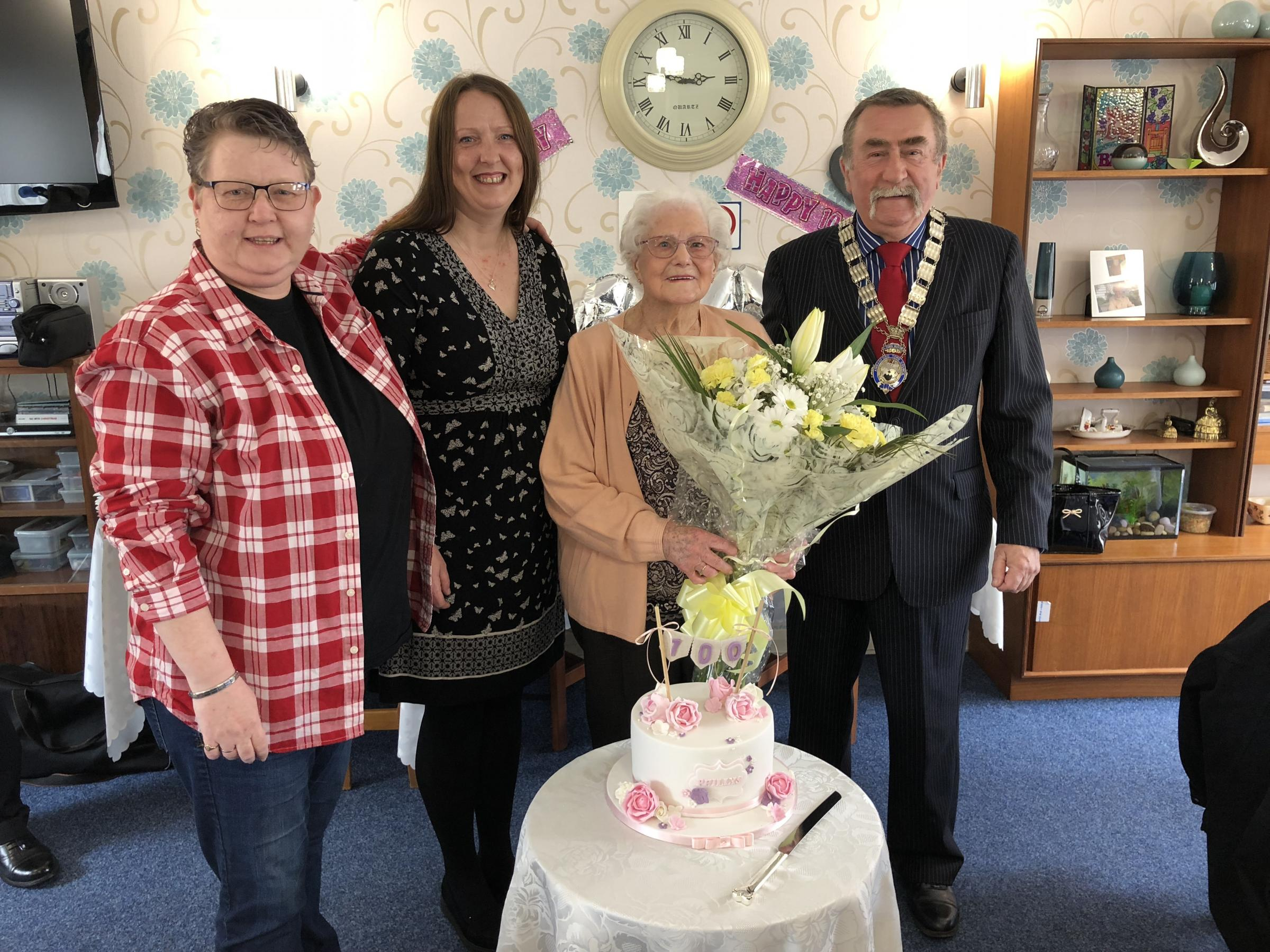 Cllr Pam Harris, Cllr Wendi Mills-Lowe and Mayor Colin Evans present 100-year-old Phylis Hobbs with a bunch of flowers.