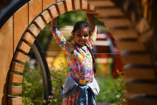 A child plays on a structure in the new Children's Garden at Kew Gardens