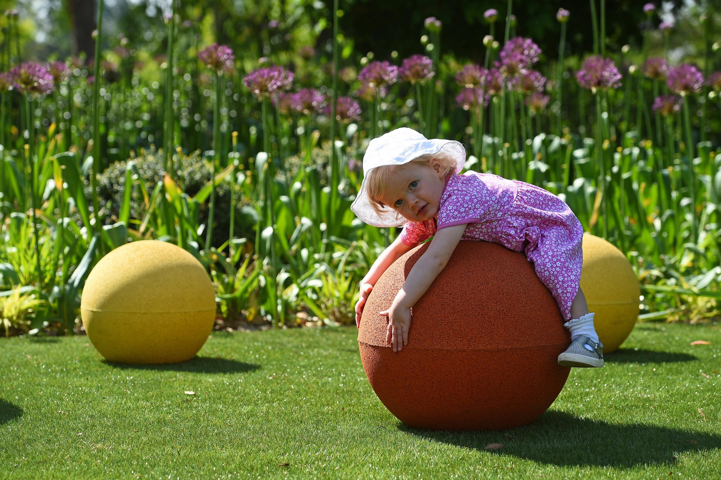 Toddler Martha White, playing on a giant ball in the new Children's Garden at Kew Gardens in Surrey